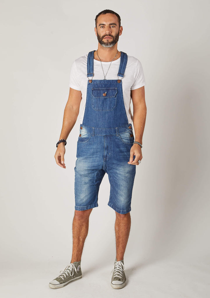 Full frontal shot of Dungarees Online's blue with slim-fit, bib-overall shorts, with view of zip fly and denim abrasions.