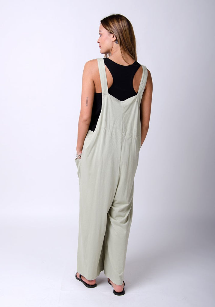 Rear, full-length model with hands in pockets wearing pale-green, cotton jersey, wide-leg overall.