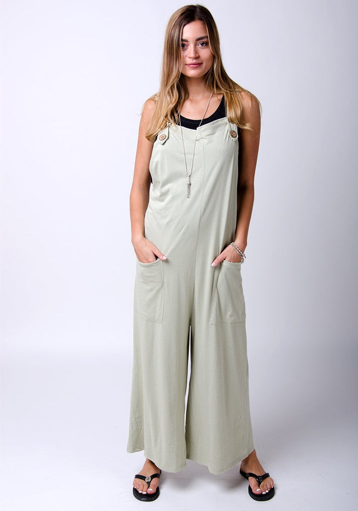 Amber-style, pale-green cotton jersey, wide-leg dungarees. Full-length pose highlighting functional pockets.