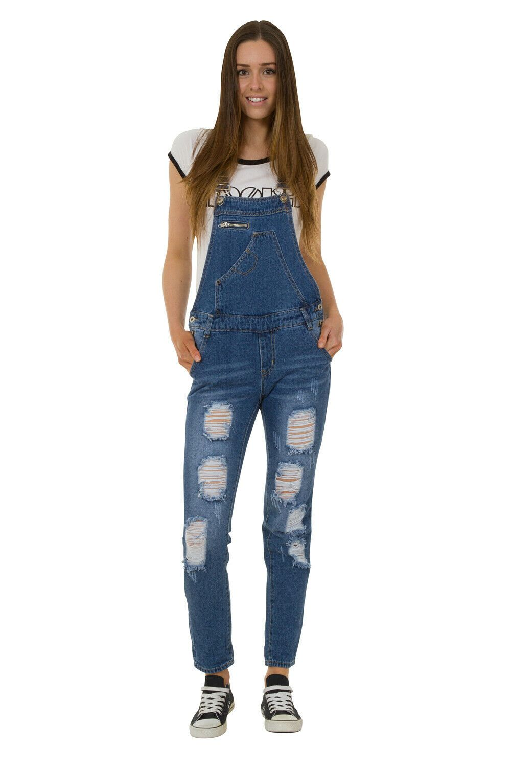 Full frontal pose with hands in front pockets of women's denim dungaree with view of asymmetrical bib pocket, zipper pocket and adjustable straps.