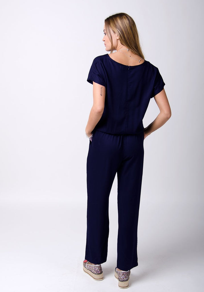 Full-rear pose looking to her left, wearing ladies blue jumpsuit with elasticated waist.