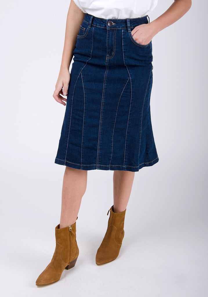 Half-front pose with left hand in pocket, wearing Kim style darkwash, soft panelled denim skirt with front zip styling.