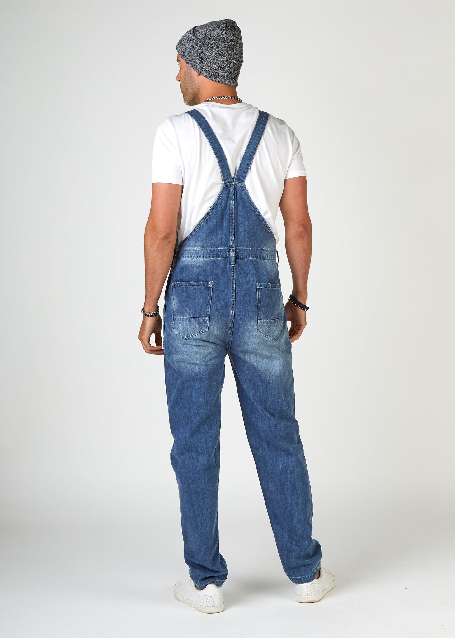 Rear full-length pose looking left, wearing Bertie-style, ripped denim bib overalls with view of back straps and pockets.