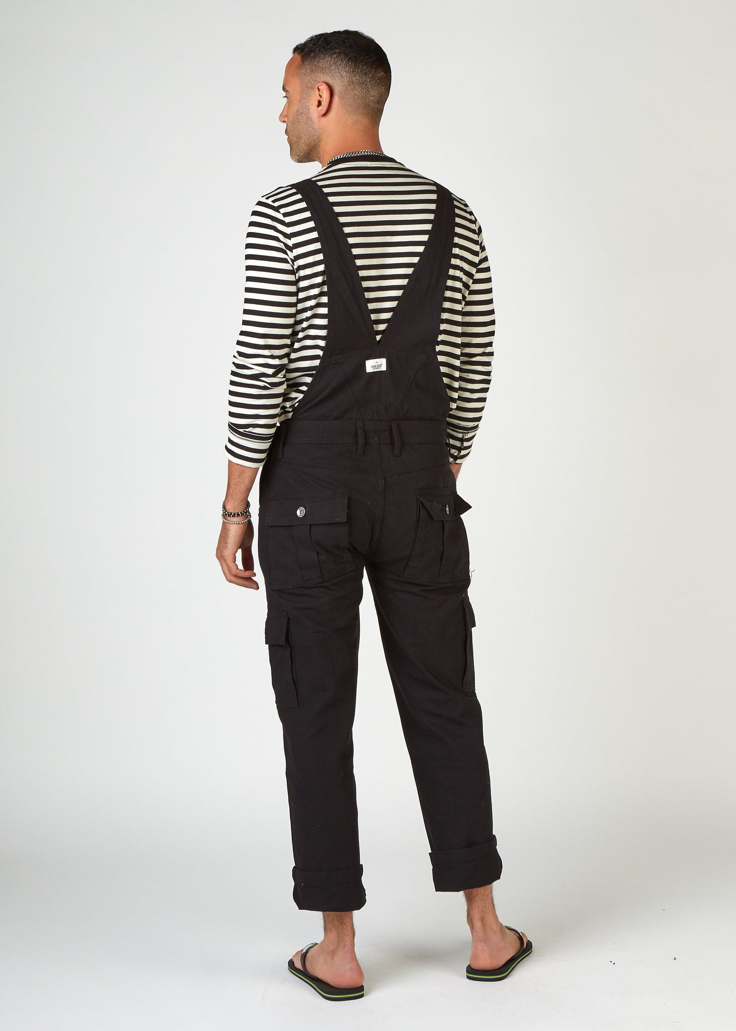 Full back pose facing slightly to left, with hand in right pocket wearing black overalls from Dungarees Online.