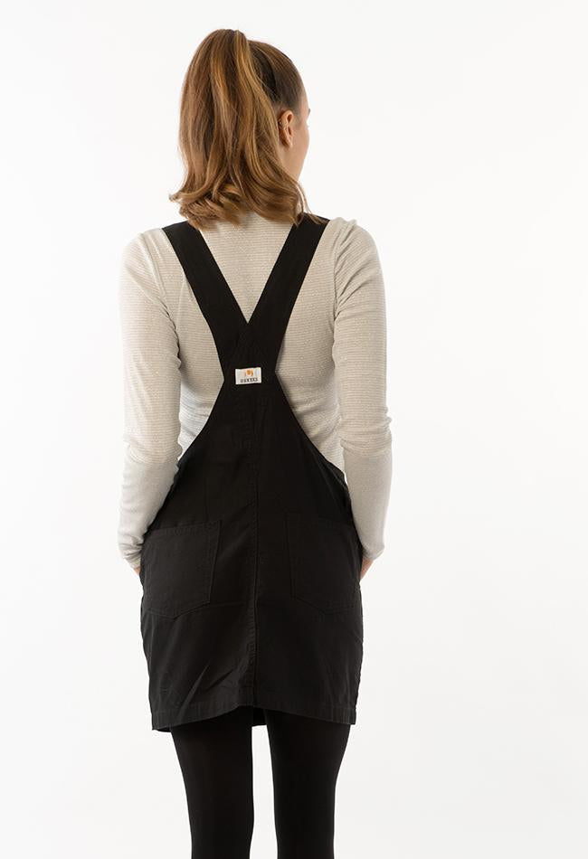 Top two-thirds rear pose, wearing women's dark loose-fit dungaree dress, focussing on back straps and pockets.