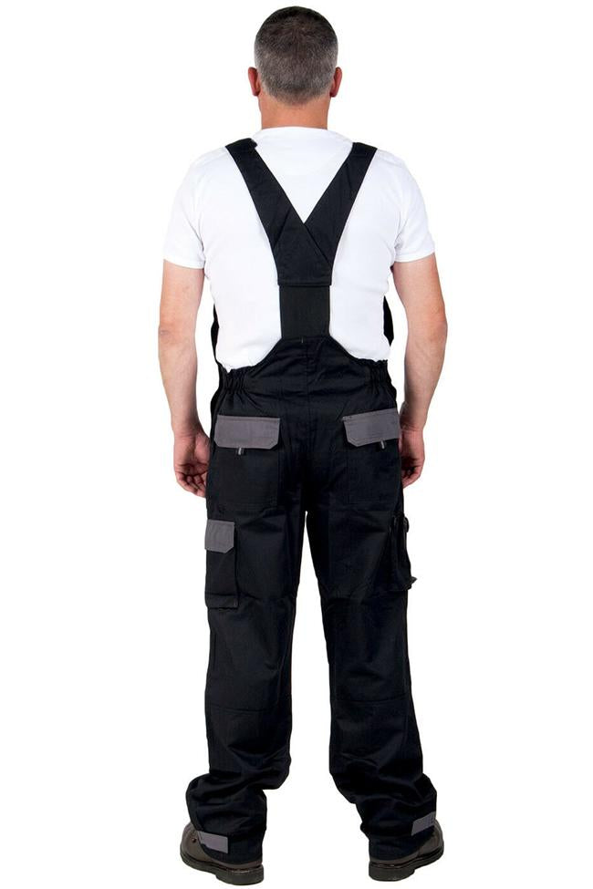 Full-length back pose wearing black polyester-cotton Portwest Texo Contrast dungaree work overalls with view of elasticated back waist and rear pockets with velcro flaps.