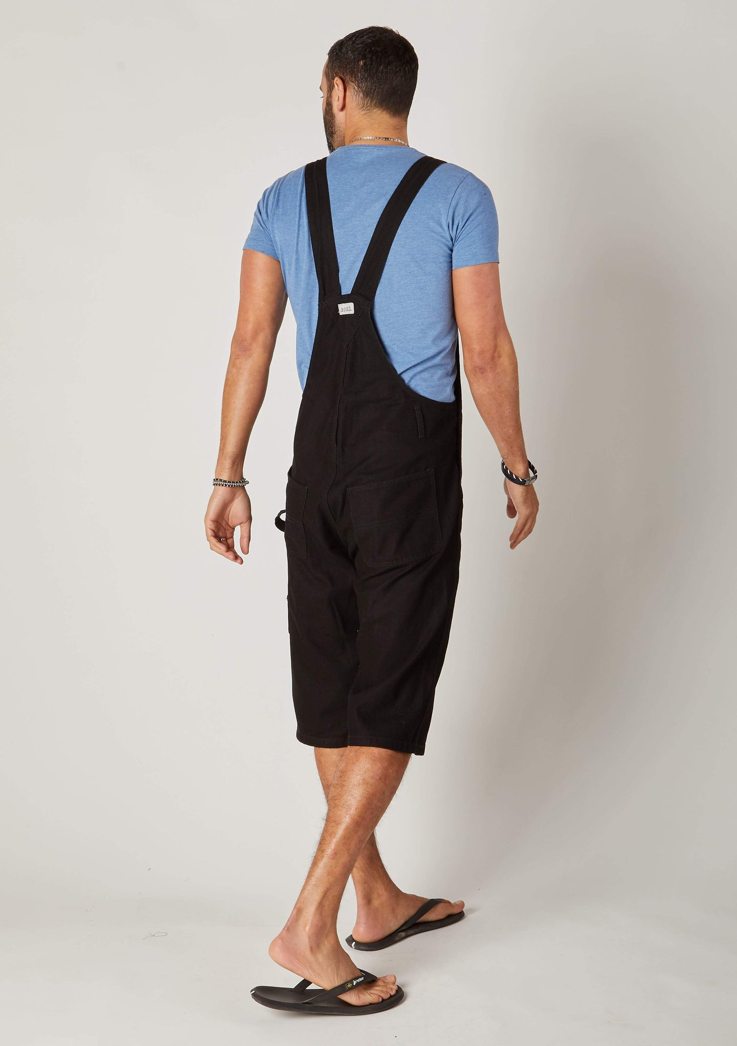 Rear twisted pose wearing 'Blake' brand black bib overalls shorts from Dungarees Online.