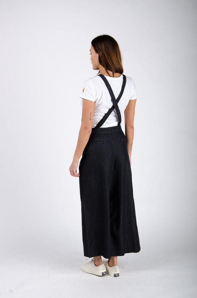 Back pose looking left focussing on cross-straps of wide-leg bib overalls.