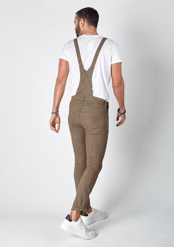 Rear pose wearing mens skinny fit dungarees with focus on cross straps.