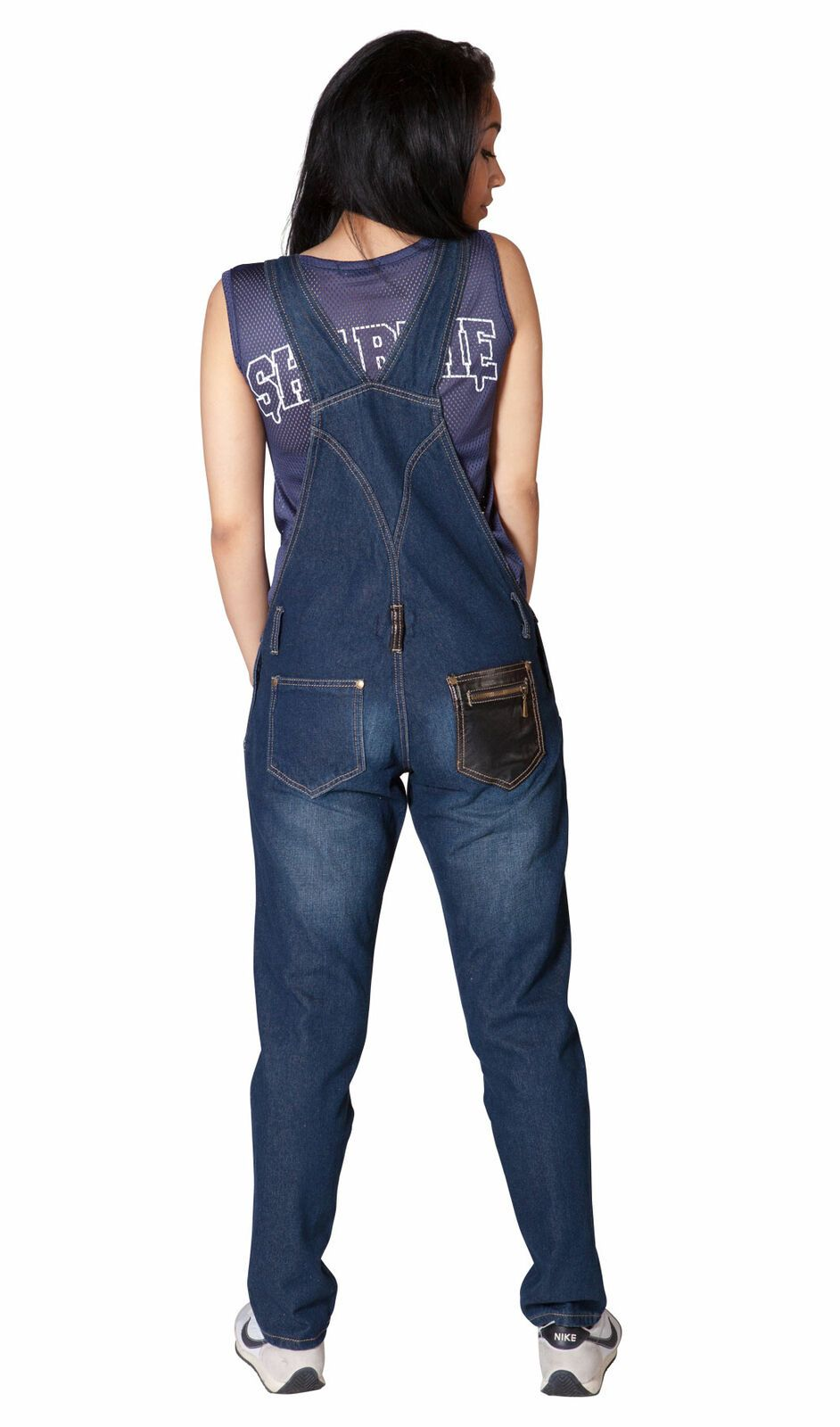 Back pose looking right with focus on back straps and pockets of indigo dungarees.