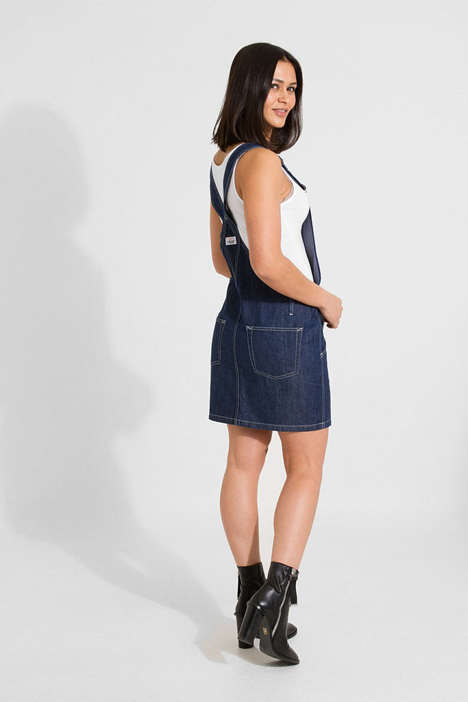 Full side-rear pose while twisting to face camera, wearing women's short denim dungaree dress in dark blue.
