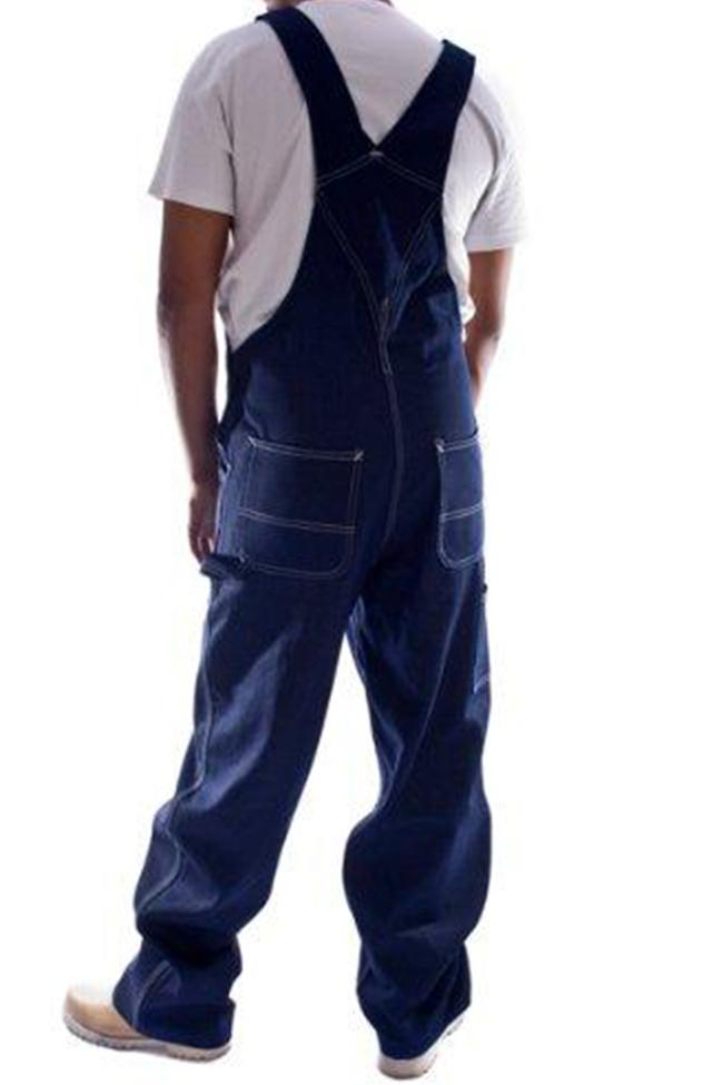Rear pose with thumbs in reinforced pockets, wearing Carhartt R08 indigo denim dungarees.