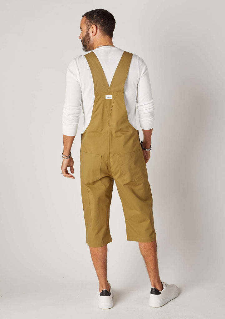 Full back pose looking left, showing rear pockets and back straps of coloured olive dungaree shorts.