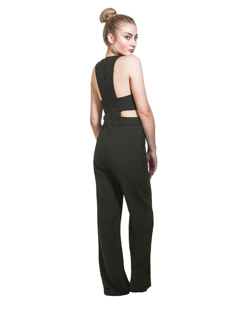 Back pose looking right with focus on wide-leg cut and back zip fastening of dark-green jumpsuit.