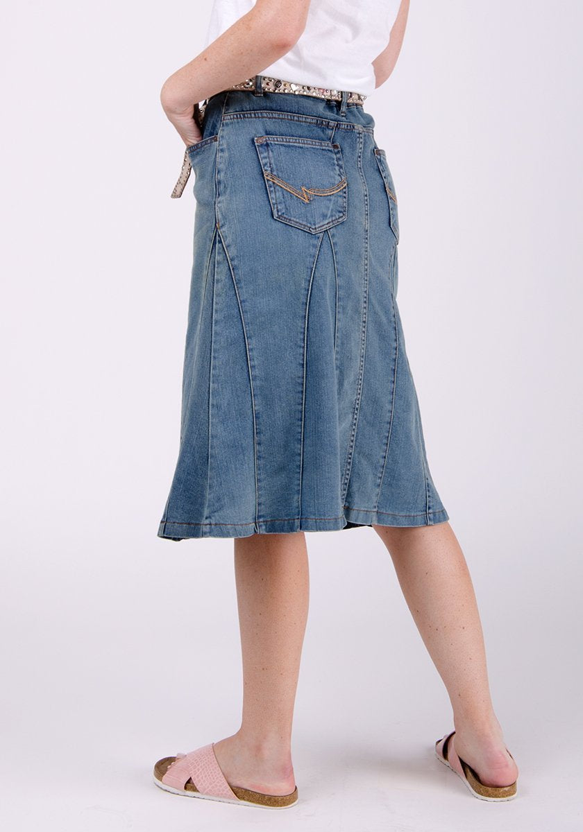 Half-rear pose wearing midwash denim skirt focussing on denim texture, panels and back pockets.