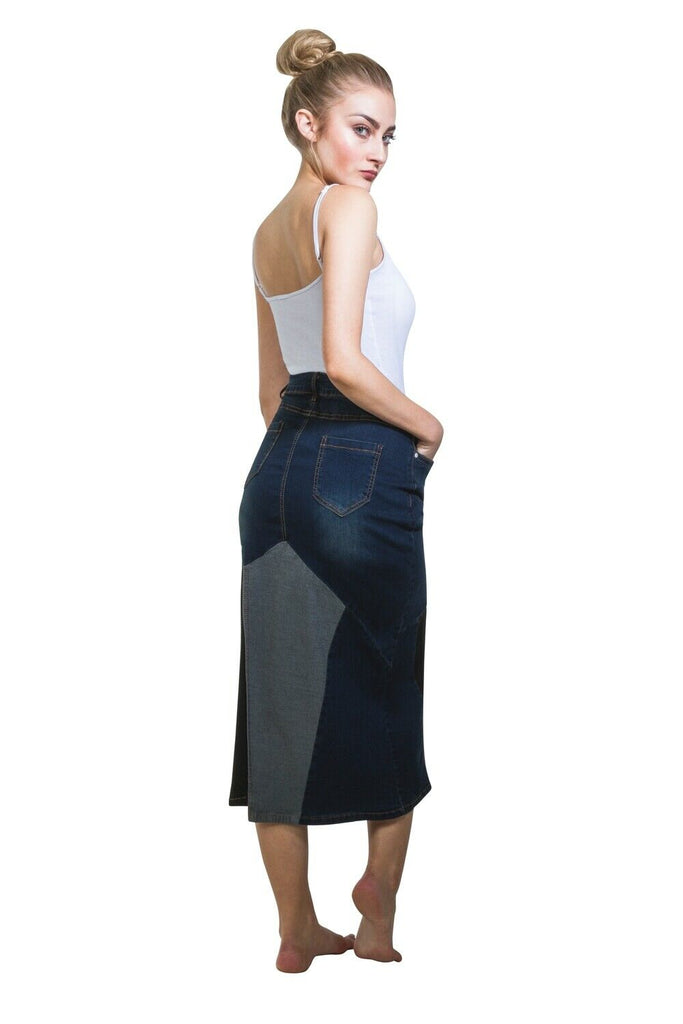 Angled rear view of indigo, black and pale blue denim midi-skirt with hands in front pockets and view of back pockets and belt loops.
