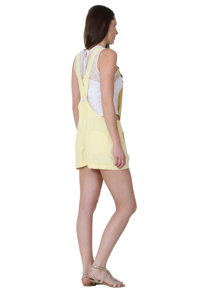 Angled rear-side pose wearing lemon, relaxed-fit bib-overall shorts from Dungarees Online.