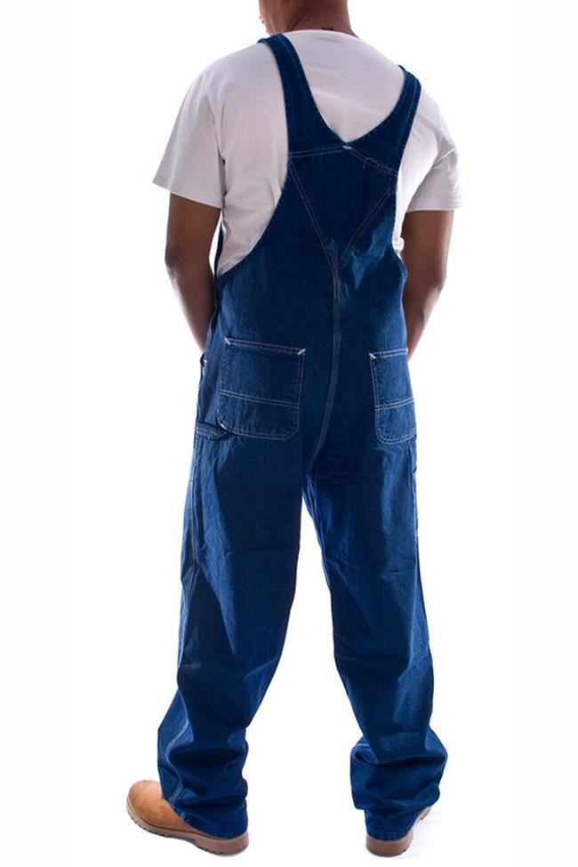 Rear pose with thumbs in reinforced pockets, wearing Carhartt R07 stonewash denim dungarees.