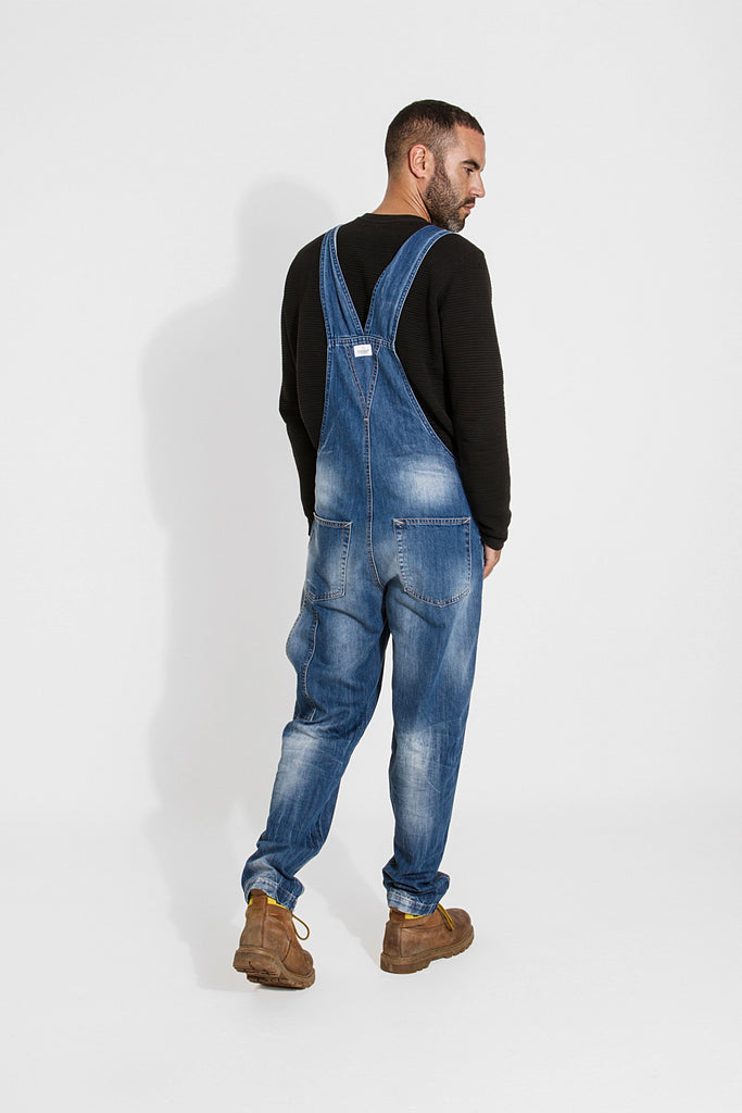 Distant full walking pose wearing 'Christopher' brand bib overalls from Dungarees Online.