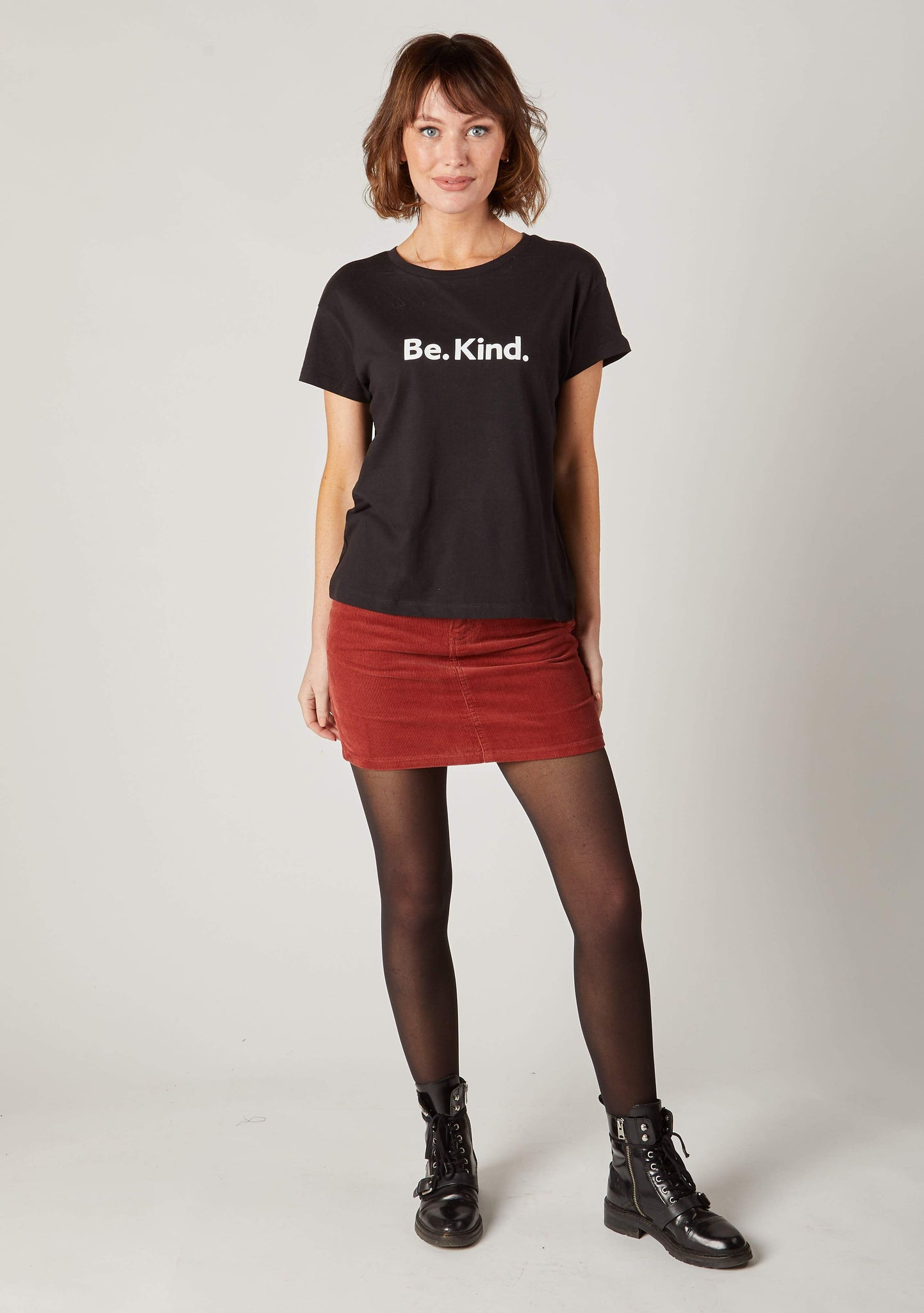 Full frontal shot of Dungarees Online's autumnal, soft-touch, red corduroy skirt with model leaning on right hip.