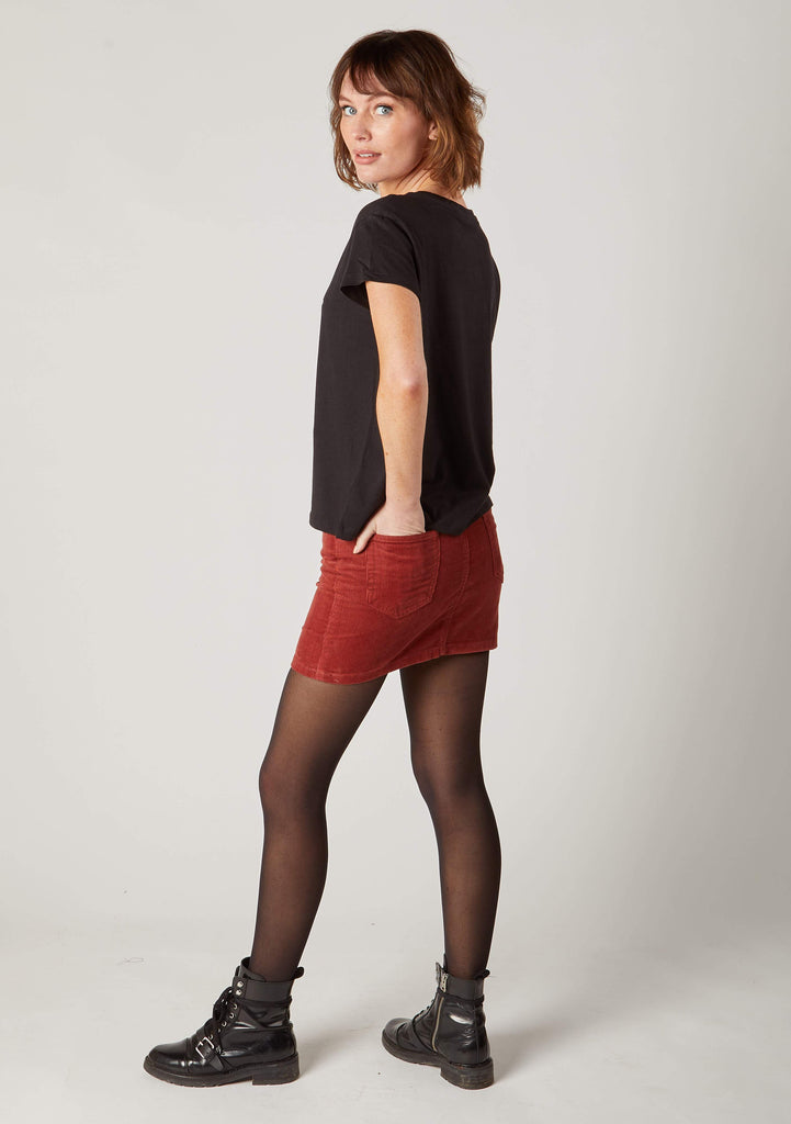 Angled side view with hand in rear-left pocket of soft, red corduroy skirt, paired with black t-shirt.