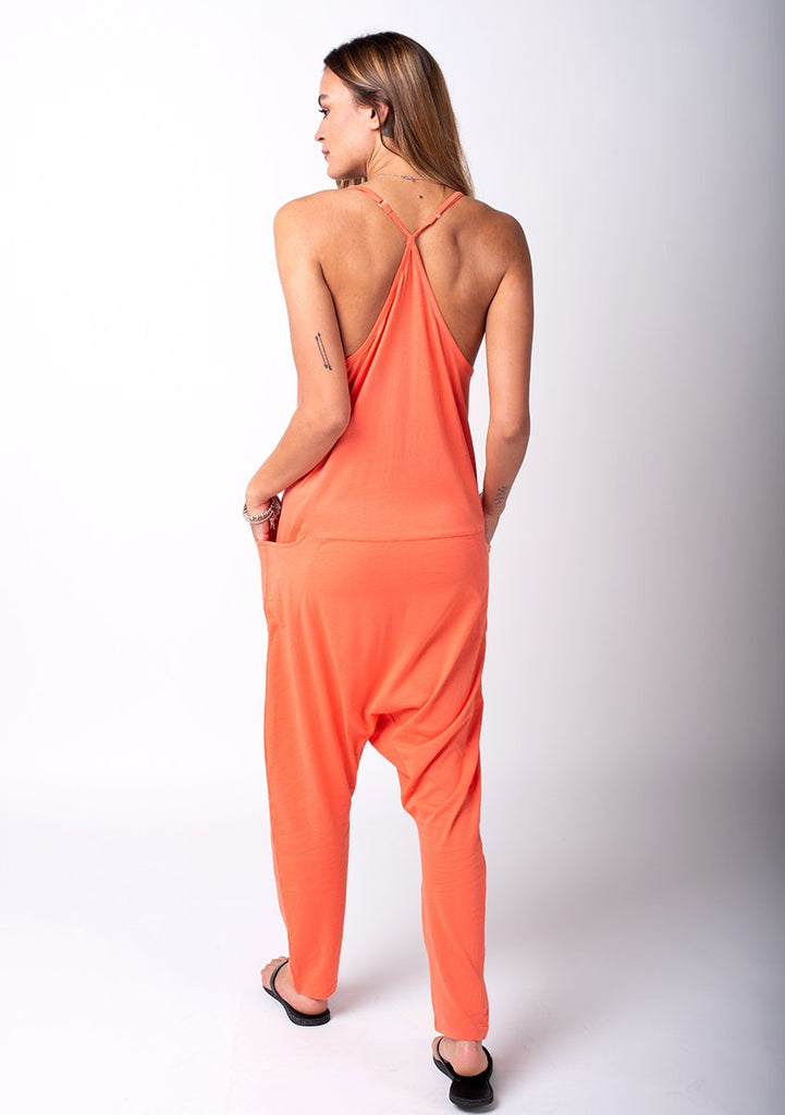 Full rear pose twisting to her left with hands in front pockets. Wearing Jools-style coral jersey jumpsuit showing crossed back straps.