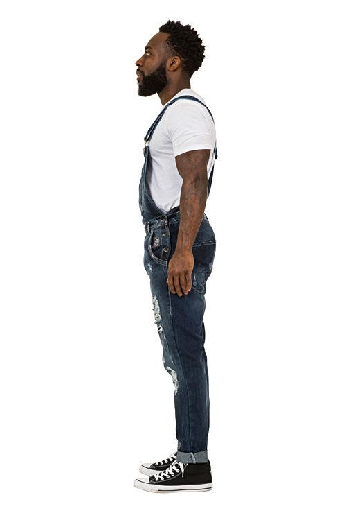Full side pose facing to his right wearing 'Alan' brand Mens Destroyed Denim Dungarees.