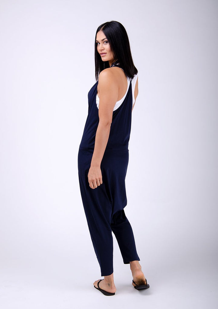 Full side pose, twisting to her left, wearing navy blue, jersey cotton jumpsuit with adjustable straps.