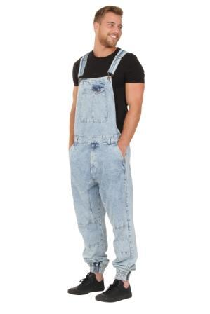 Front-side view of model with hands in front pockets of light blue, acid wash dungarees.