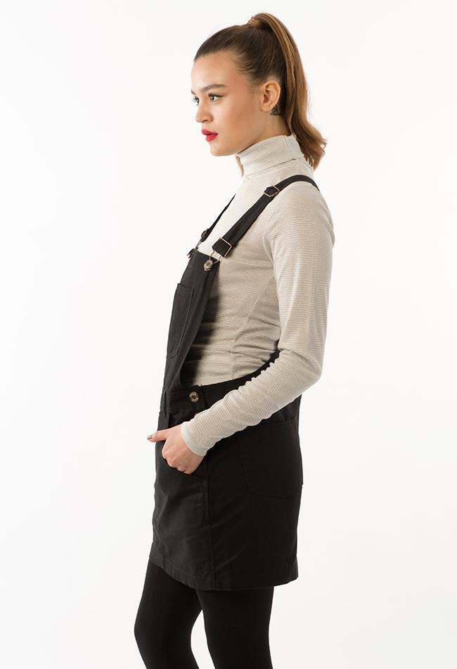 Full side view of Cicely women's black denim bib-overall dress with hands in front pockets.