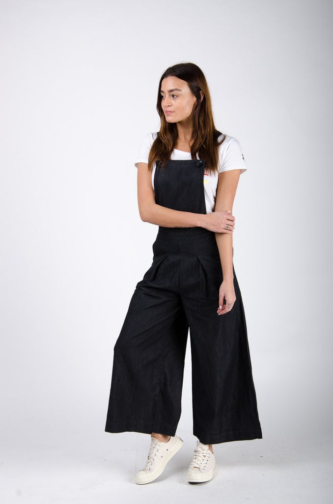 Side pose looking right wearing black wide-leg bib overalls.