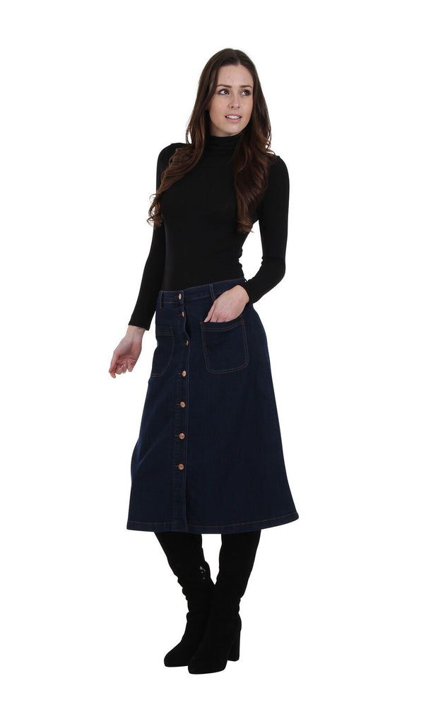 Angled frontal view leaning on right hip with hand in front-left patch pocket of dark denim button-front skirt.