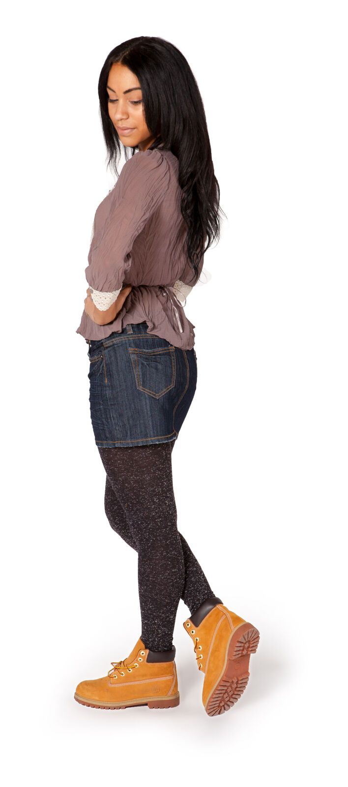 Full-length side view of short, indigo, medium weight denim skirt with clear sight of back pockets and belt loops