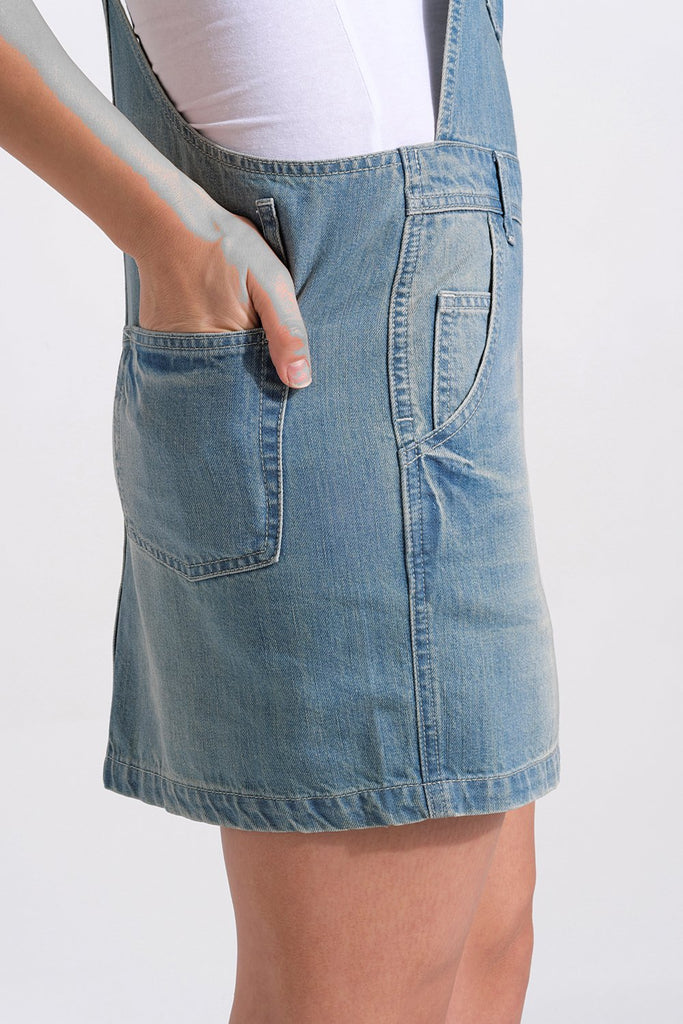 Side close-up of short denim dungaree dress focussing on front and rear pockets, with right hand in right rear pocket.