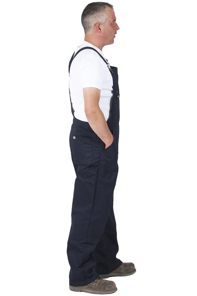 Full side pose with hands on side pockets of Dickies black work overalls with side button fastening.