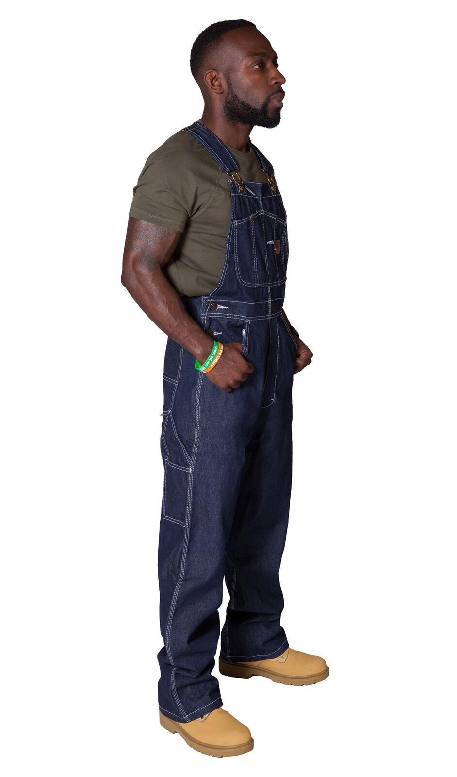 Full side pose wearing American indigo work dungarees showing side button fastening.