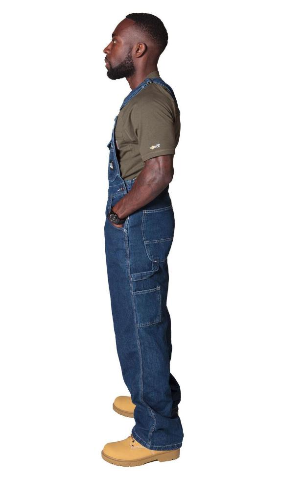 Full side pose wearing work dungarees showing side button fastening.