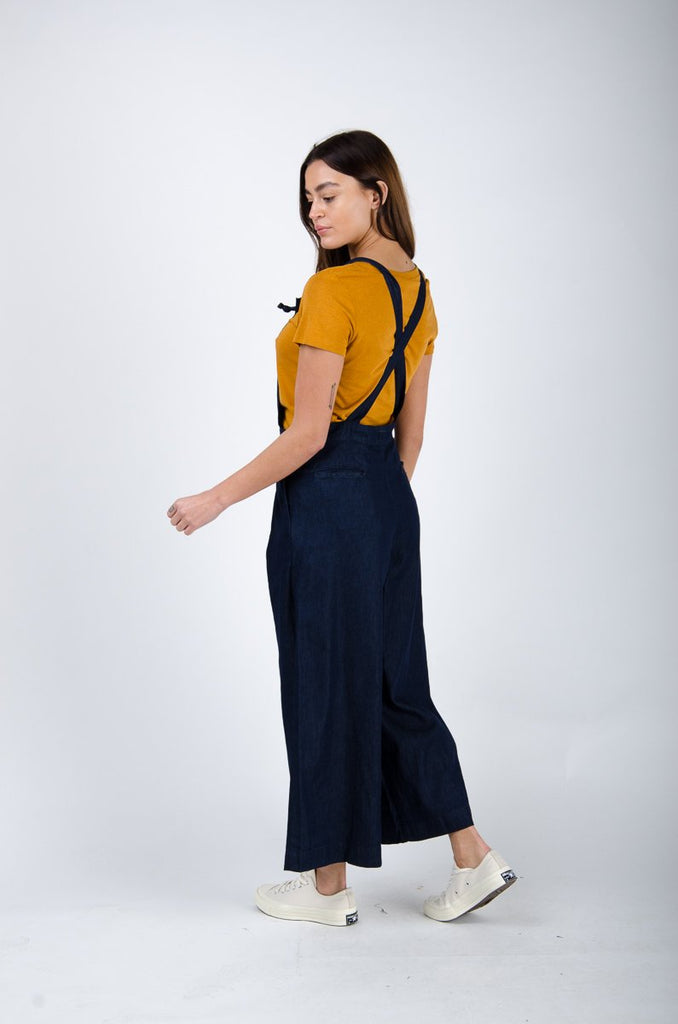 Side pose twisting to left wearing wide-leg bib overalls.