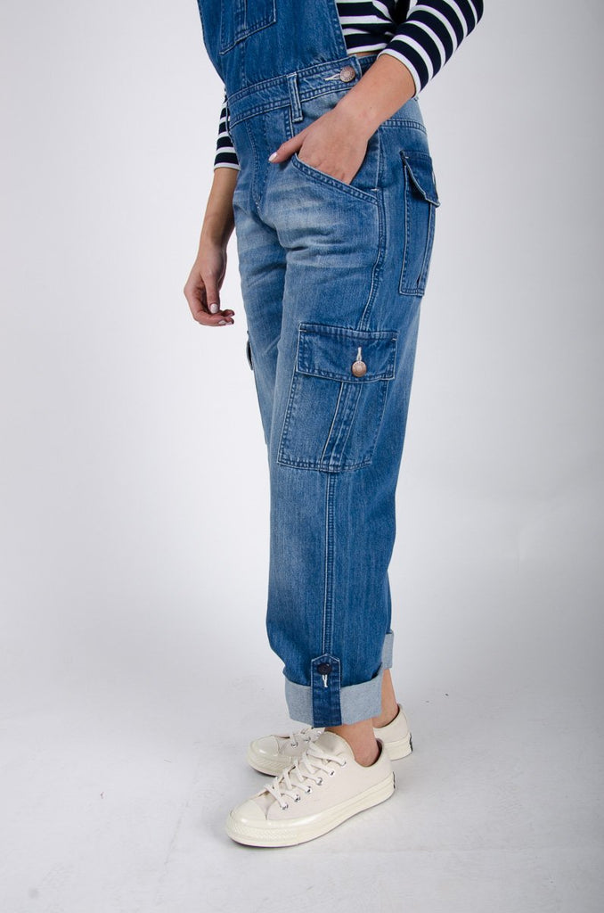 Bottom two-thirds side pose with hand in front left pocket, wearing women's Daisy dungarees with front, back bib and cargo pockets.