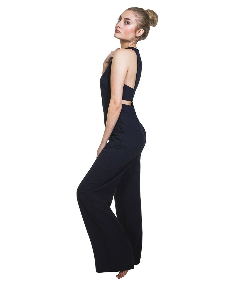 Half side pose looking right with hand in front pockets. Focus on wide-leg cut and back zip fastening of navy jumpsuit.