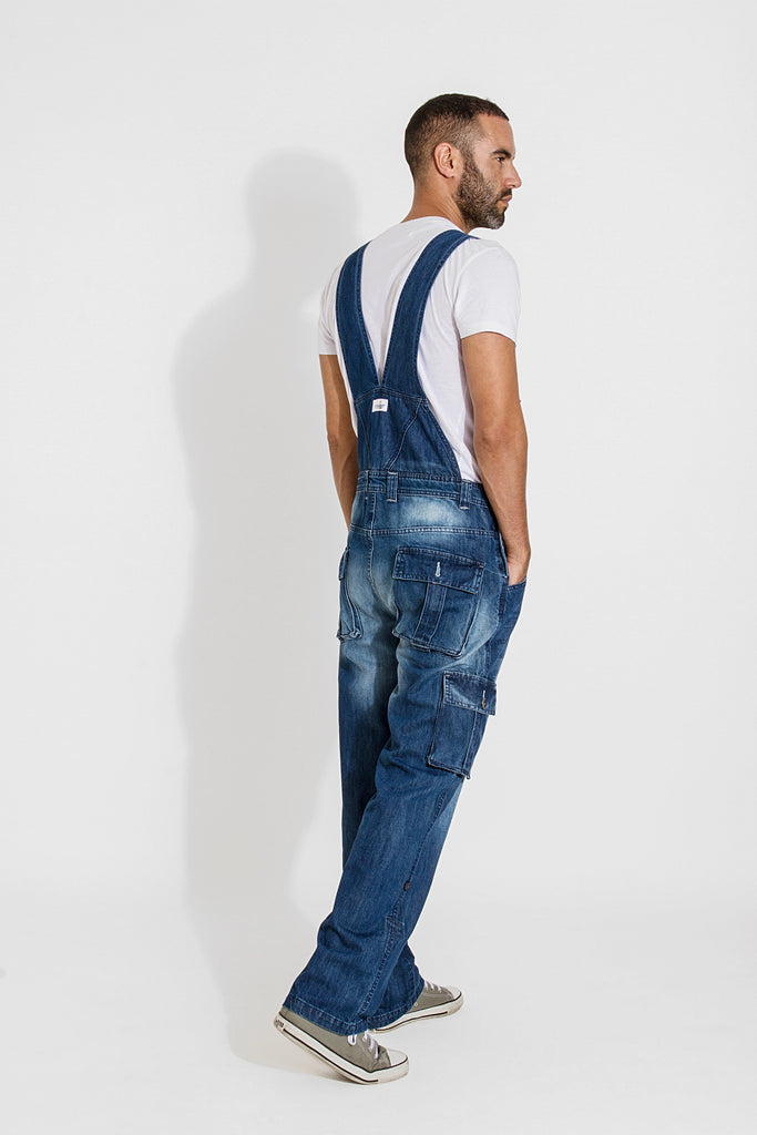 Full side-back pose facing to his right, with hands in pockets wearing midwash overalls from Dungarees Online.