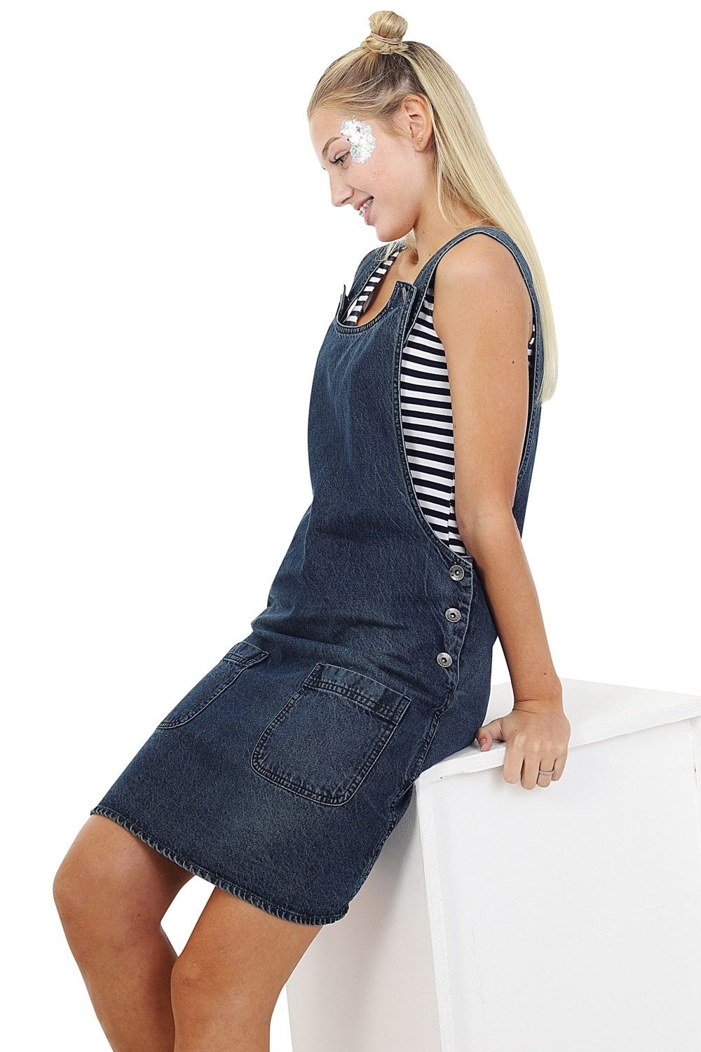 Leaning against box showing elegant, 3-button side fastening and front pockets of sleeveless jean dress.