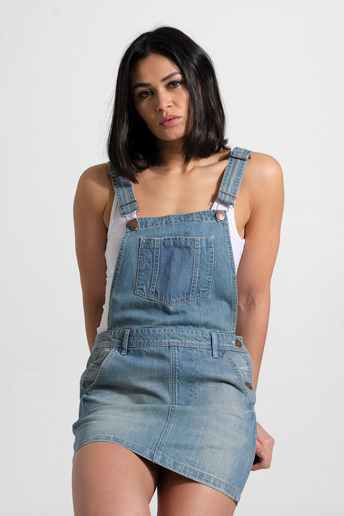 Sitting or leaning pose, looking straight ahead with hands tucked under backside, wearing bib-overall denim dress with focus on adjustable straps.