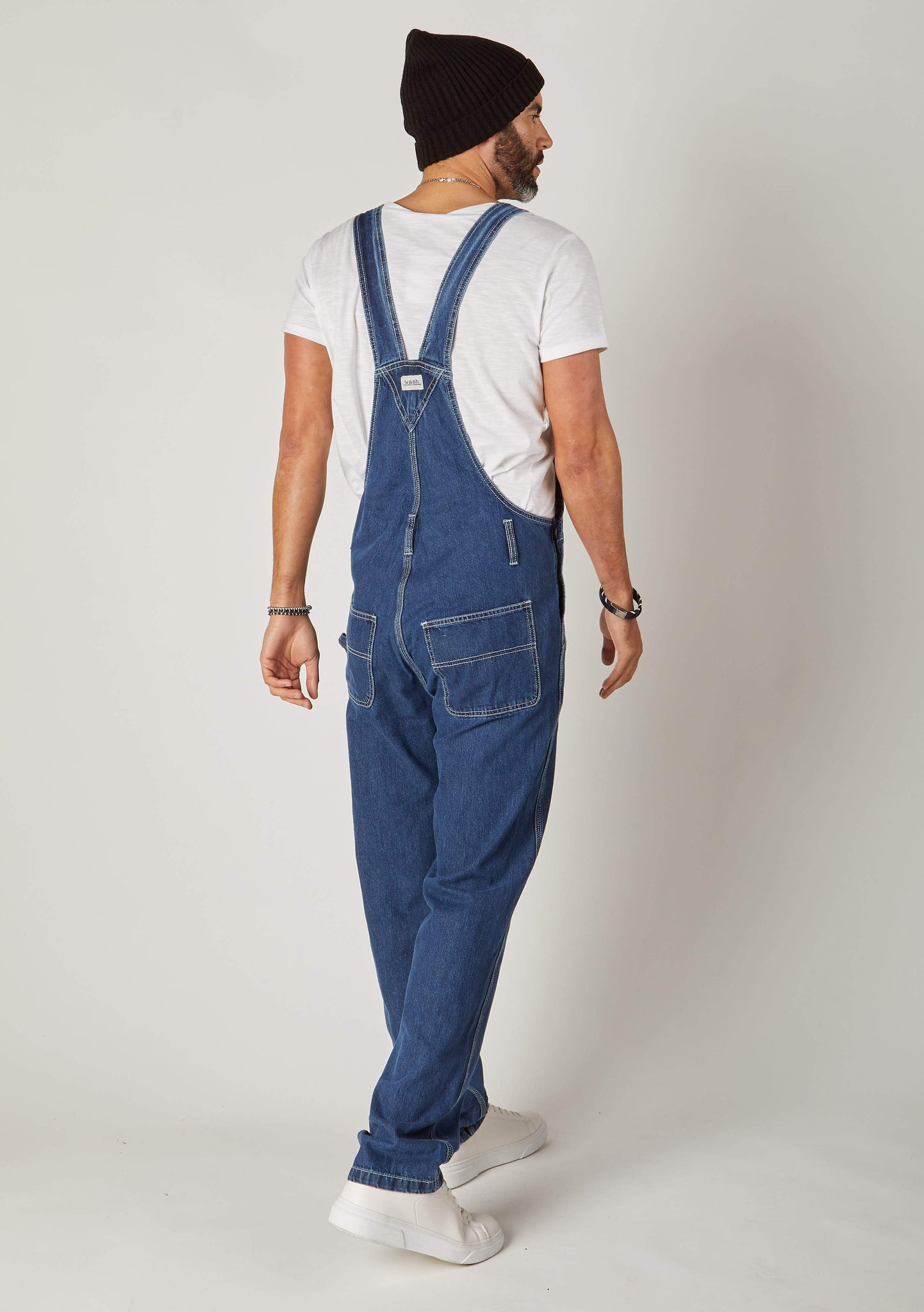 Full rear pose, angled to his right, wearing contemporary 'Maddox' stonewash 10oz denim dungaree overalls with view of back pockets and straps.