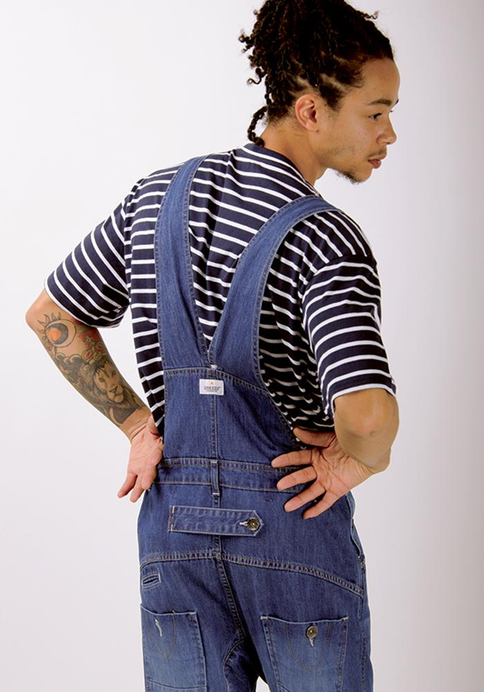 Focus on rear of dungarees focussing on adjustable waist and belt loops of lightwash dungarees.