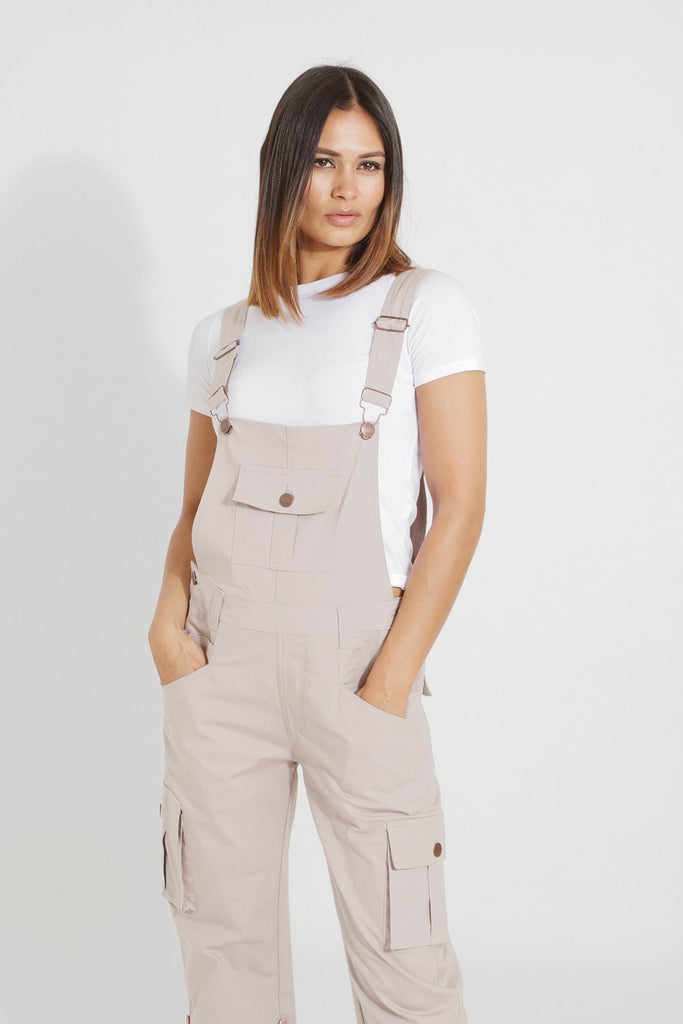 Top half front view of old school beige cotton dungarees with hands in both front pockets from Dungarees Online.