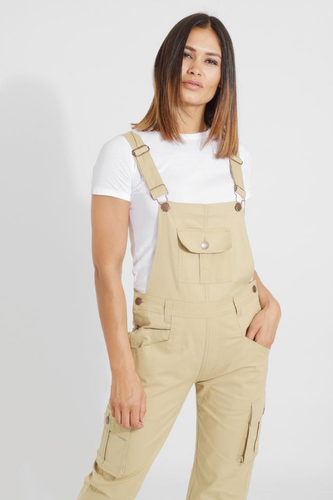 Front view with bottom of legs cropped, wearing old school, sandy coloured cotton dungarees. Standing with weight on left hip and hand in left pocket.