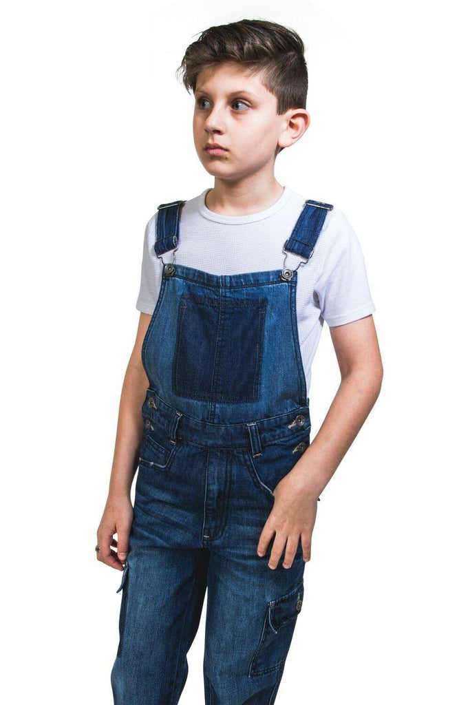 Slightly angled frontal view of kids' denim deconstructed dungarees with hand in left pocket.