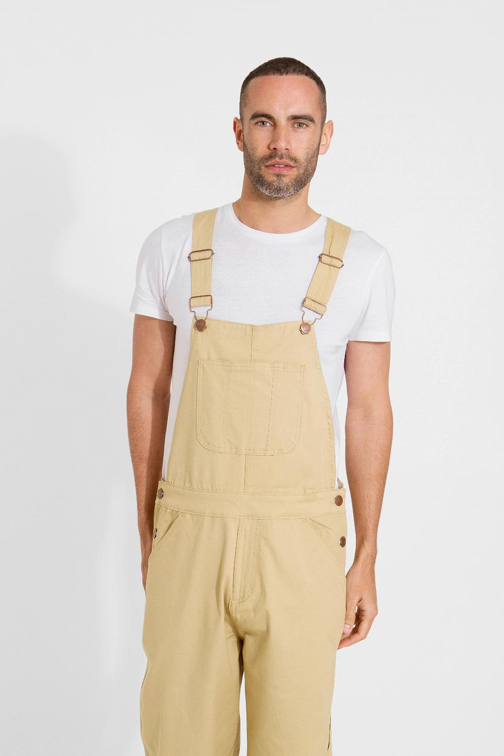 Frontal pose cropping bottom third, wearing loose fitting cotton dungaree shorts, with focus on side buttons and adjustable straps.