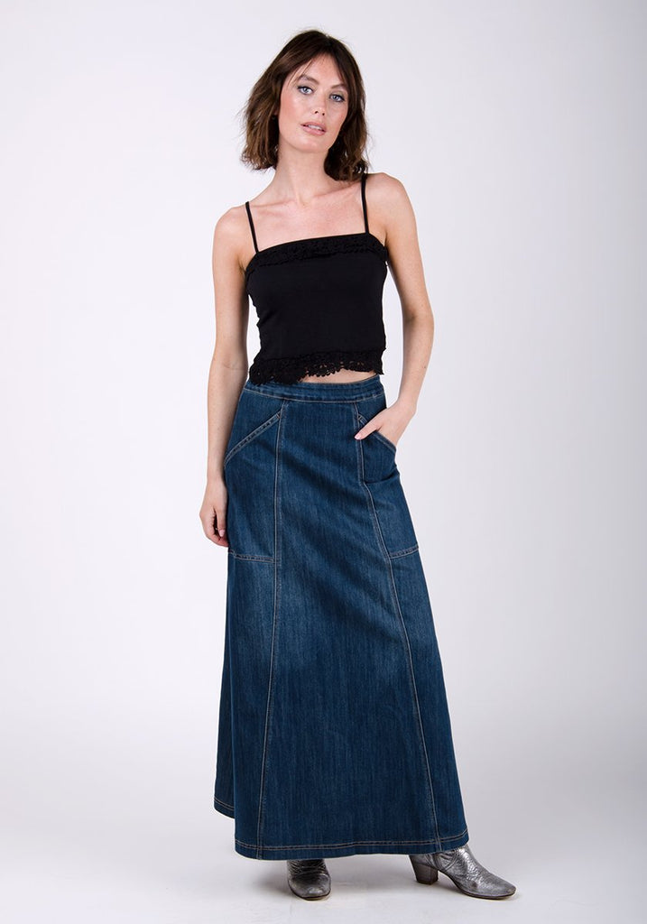 Full-frontal pose with left hand in deep utility pockets wearing Heather style vintage wash denim skirt.